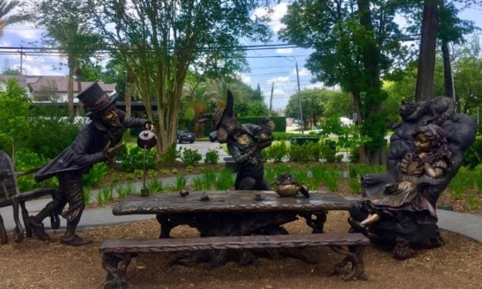 Art sculpture of Mad Hatter, White Rabbit and Alice at a table in Evelyn's Park Conservancy in Houston