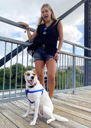 A young woman and her dog pose for a photo overlooking the river on the Faust Street Bridge in New Braunfels, Texas.
