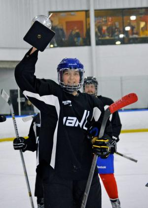 Hockey Player holds up trophy at Bill Gray's Ice Plex