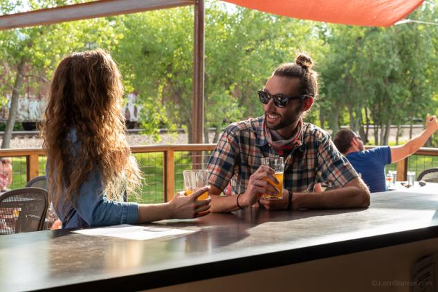 Couple drinking glasses of beer at Sanitas Brewing