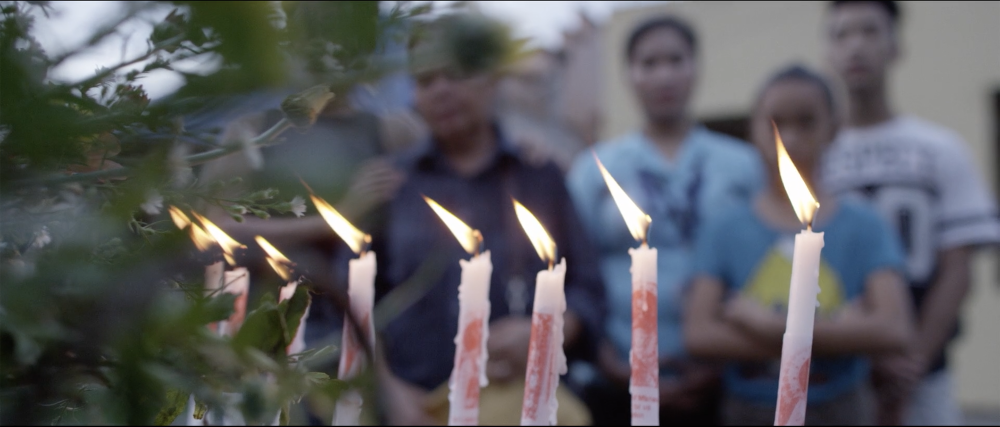 Call Her Ganda film still showing people behind lit candles