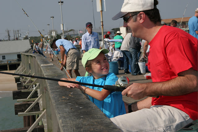 Father and daughter fishing off Kure Beach pier
