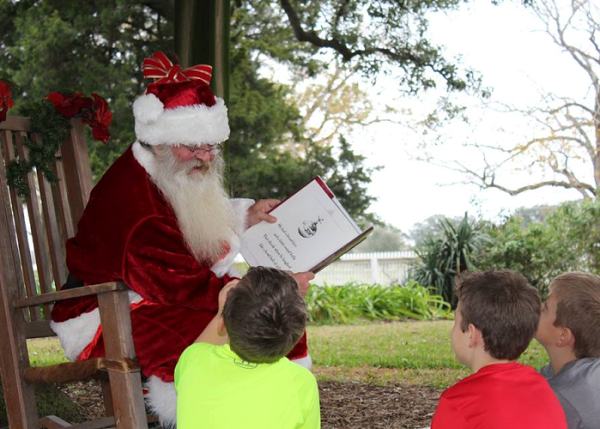 Santa reading a book to kids during Christmas at the Park at George Ranch Historical Park.