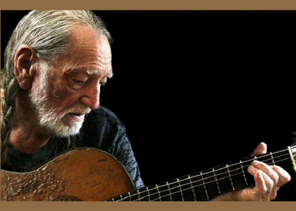 Willie Nelson playing the guitar.