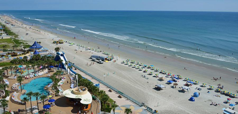 An aerial view of Daytona Beach with bright blue water and blue and yellow umbrellas