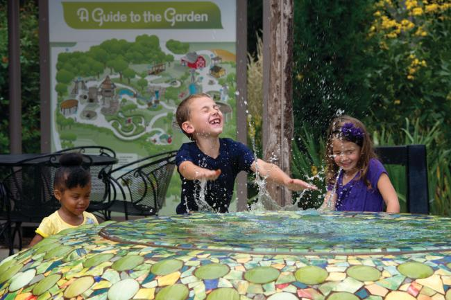 Three kids play in a water feature at a garden in Botanica Wichita