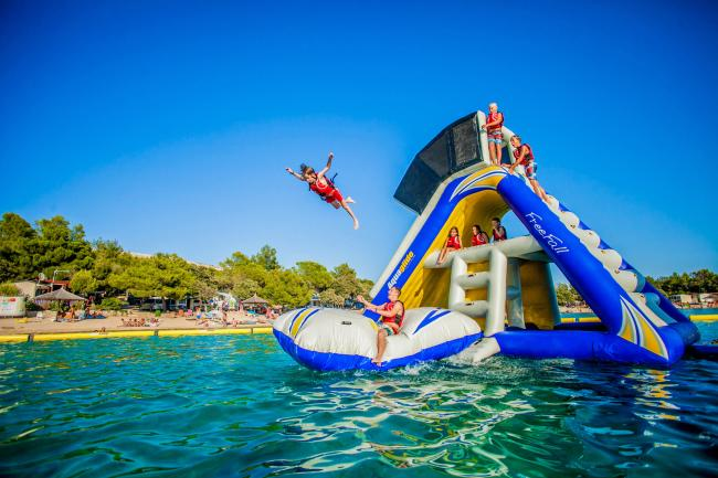 Kids play on a tall, inflatable playset that floats on the water at Splash Aqua Park
