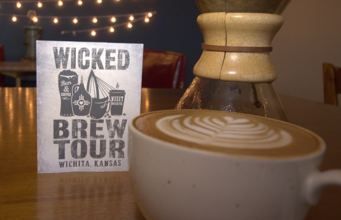 A full mug of coffee and a table-top sign sit on a table at Ecclesia. The sign includes details for the 2019 Wicked Brew Tour in Wichita.