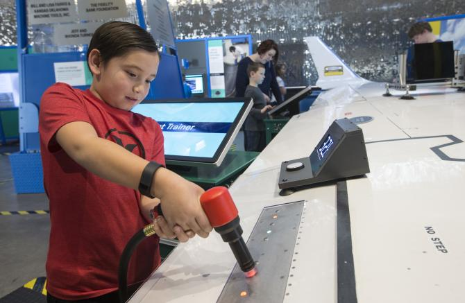 A young boy works on an aircraft wing at an interactive exhibit at Exploration Place