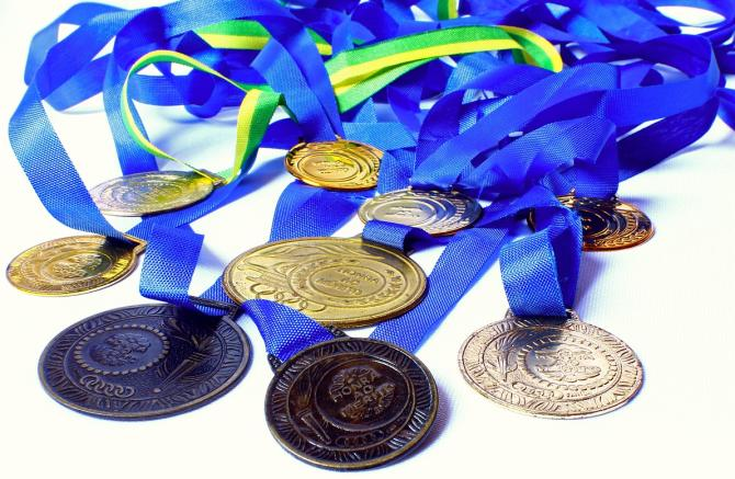 About ten marathon medals with blue ribbons sit in a pile