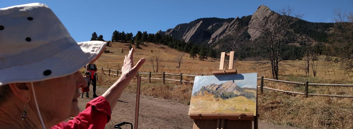 Painter painting the Flatirons Boulder