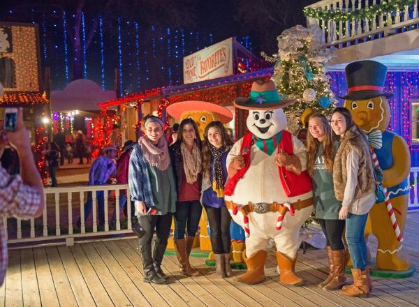 A group of girls poses with Frostbite the Snowman at Santa's Wonderland