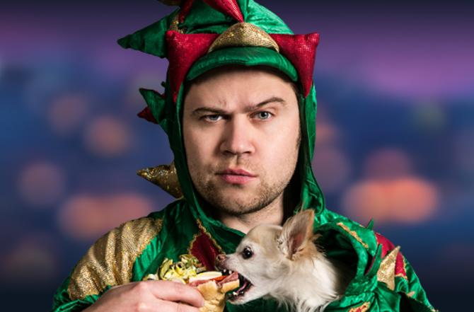 Comedian Piff the Magic Dragon wears a dragon costume and looks awkwardly at the camera while his chihuahua takes a bite of his sandwich