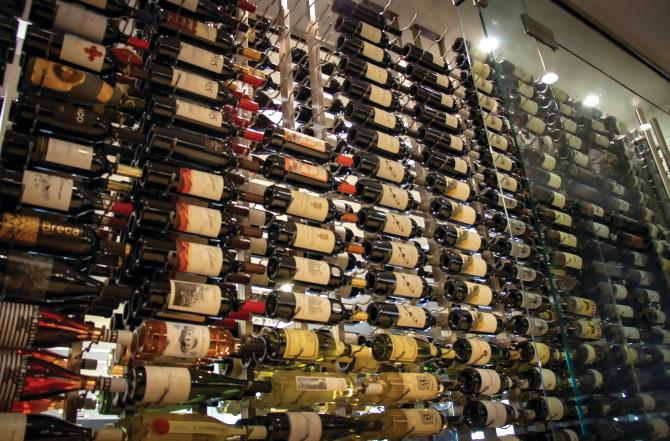 A wall of full wine bottles on display