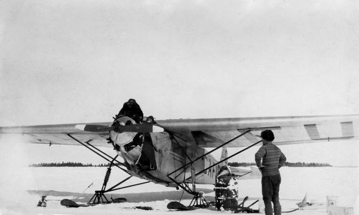 Black and white photo of old bush plane on skis, parked on a frozen lake