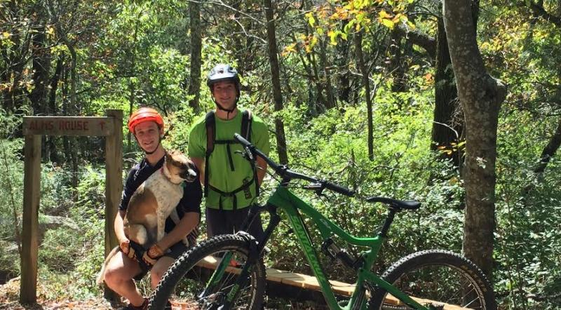 Two mountain bikers and a dog at the Land Trust of North Alabama