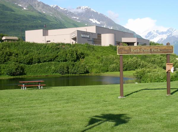 A pond, a small park, and a building on a hill