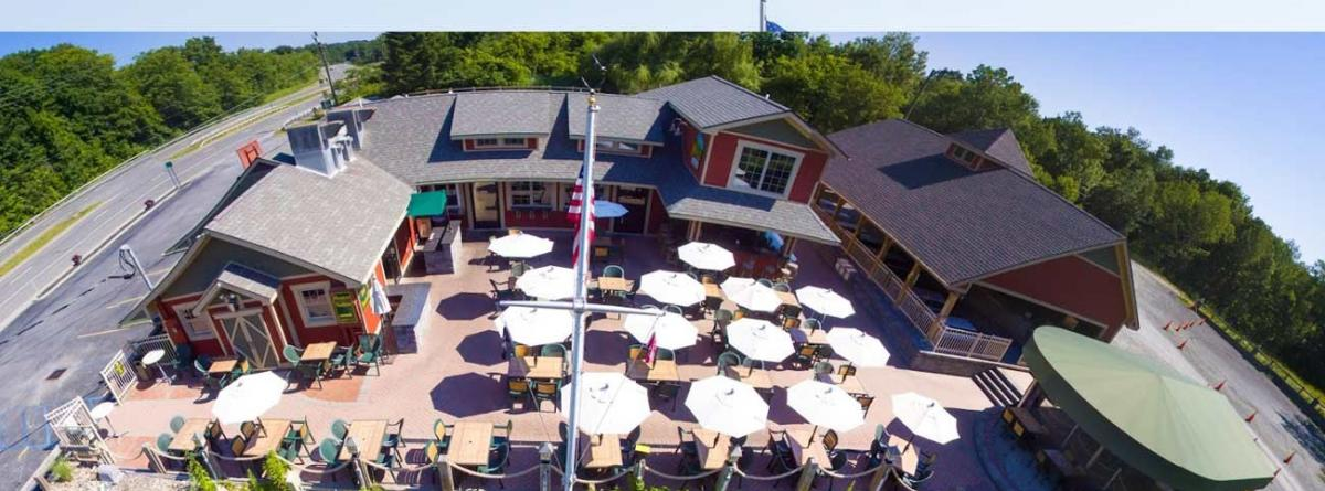 Aerial shot of Mill on Round Lake's patio with white umbrellas
