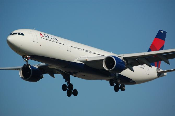 A Delta airplane descends in the sky and prepares for landing in Wichita
