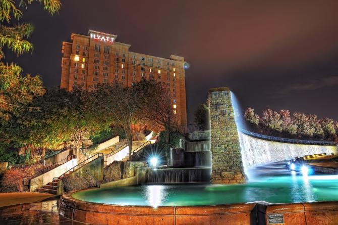 A shot of the water wall fountain and stairs at night with the Hyatt Regency hotel in the background
