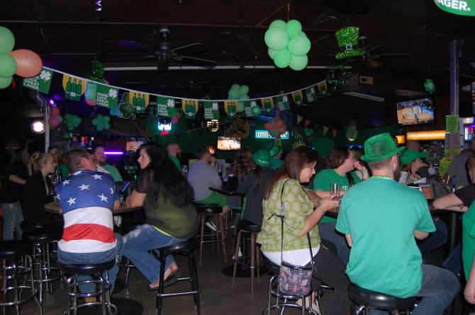 A packed crowd of St. Patrick's celebrators wearing all green fill O'Malley's in Wichita and drink green beer