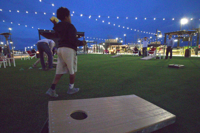 A young boy plays bag toss in the evening at Chicken n Pickle in Wichita