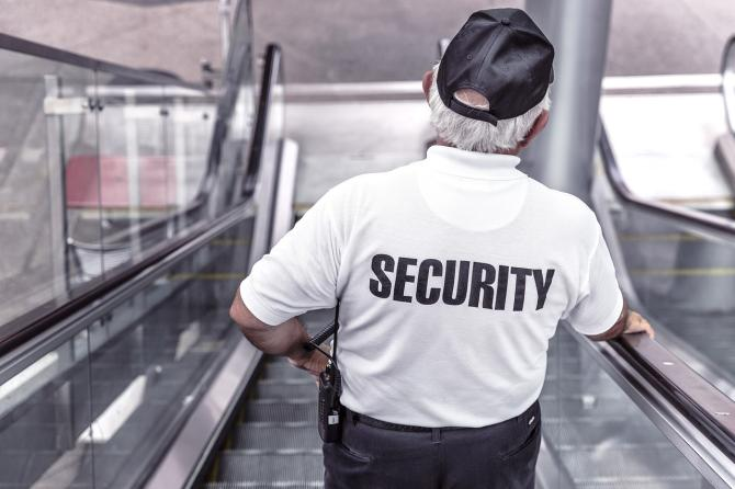 The back of a security guard descending on an escalator