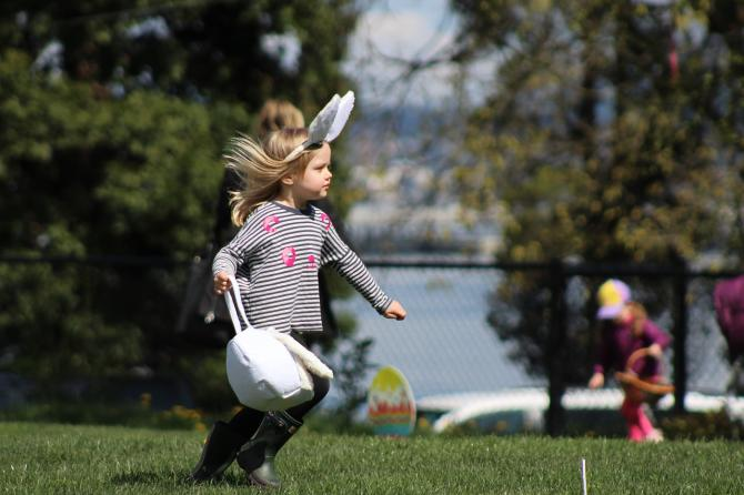 A young girl runs through a yard looking for Easter eggs with a backet in hand and bunny ears on her head