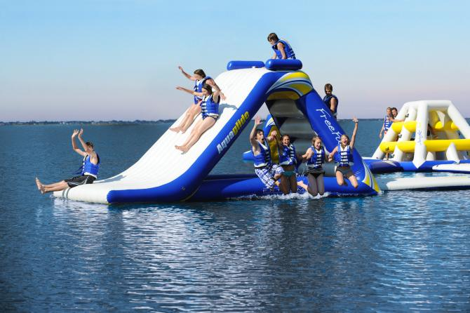 Kids slide down an inflatable slide in a lake while other kids jump into the lake off the side
