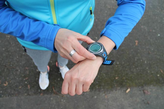 A runner stops her watch to check her time after a Wichita marathon