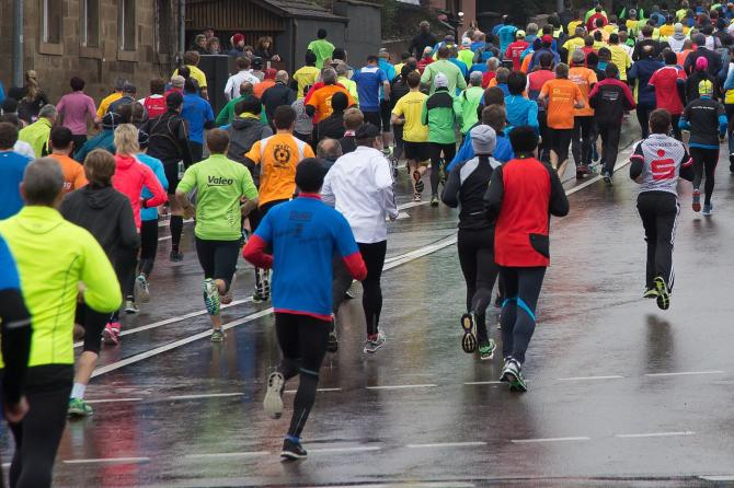 Marathon racers run through a wet street on a spring day
