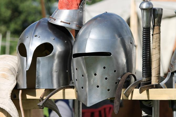 Two battle-ready helmets sit on a shelf with swords in a shop at the Renaissance Faire