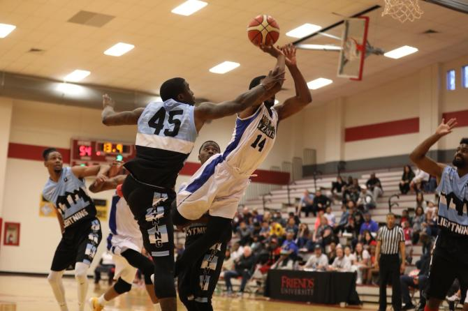 A Wichita Wizard player stretches to pull off an acrobatic shot under heavy opposition pressure