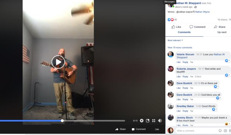 A screen shot of a Facebook Live video, one man plays guitar standing in a room and singing into a mic