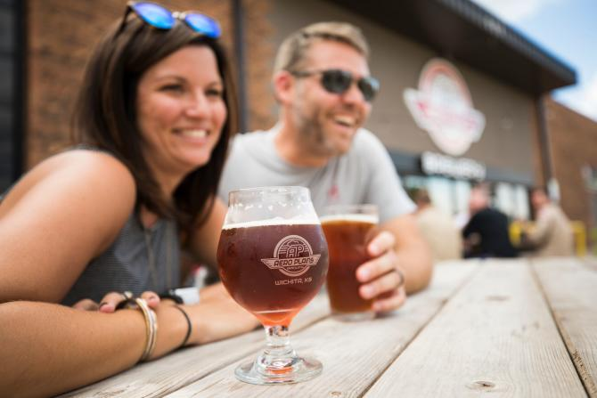 A couple enjoy beers on a patio from Aero Plains Brewery in Wichita