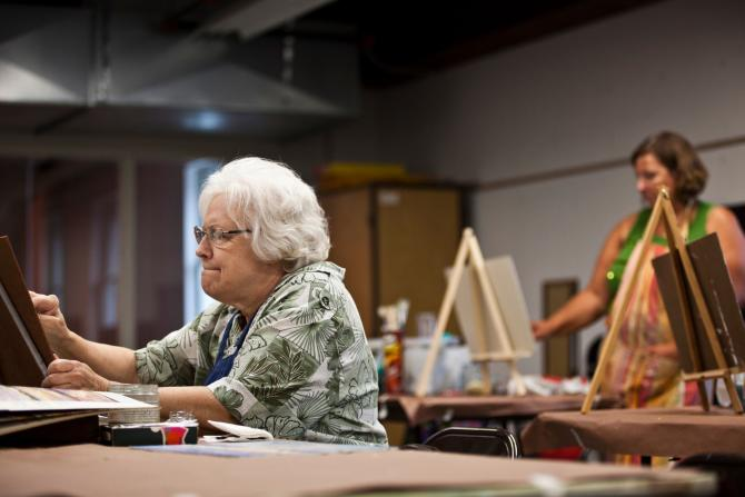 An elderly woman focuses on her painting at CityArts in Wichita