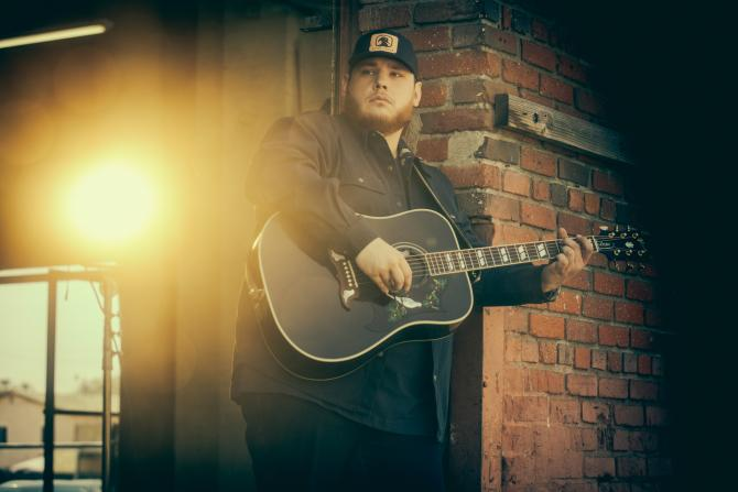 Country star Luke Combs plays his guitar and leans against a brick building