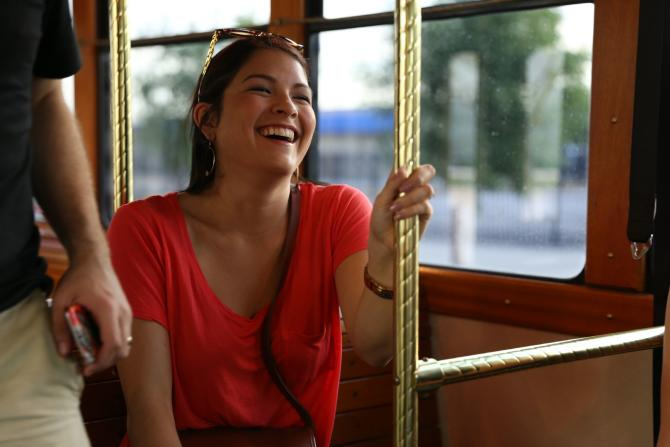 A woman laughs with her friends while riding the Q-Line
