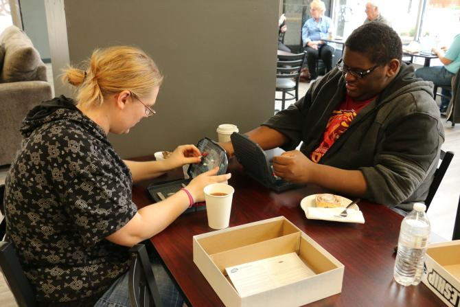 Two people sit at a table and play the Battleship board game at Sente in Wichita