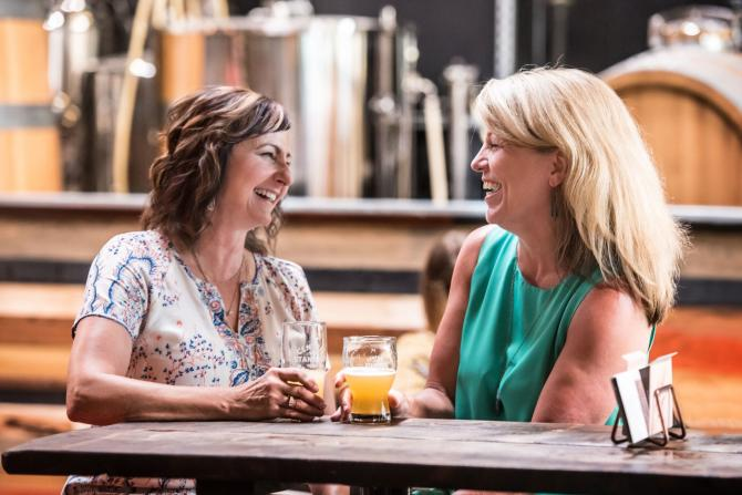 Two women tell stories at a table while enjoying freshly brewed beers at Central Standard Brewing in Wichita, Kansas