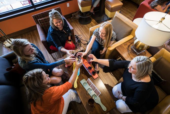 A group of women cheers with wine at Cocoa Dulce in Wichita