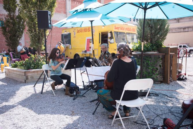 Three musicians sit around a table and lay instruments with a food truck in the background