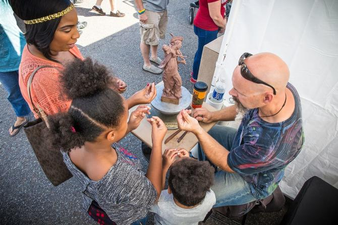 A family interacts with an artist while he creates a small statue out of clay