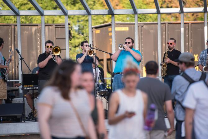A local band plays live music on an outdoor stage for Final Friday
