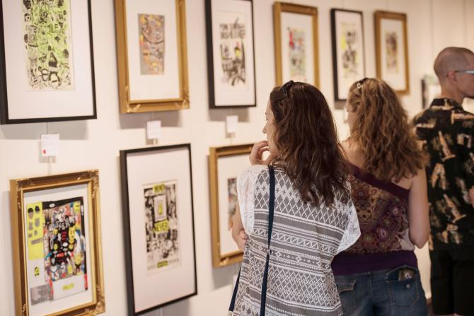 Two women examine artwork hung on a wall in an art gallery
