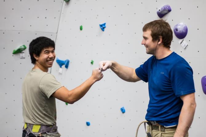 Two guys bump knuckles before climbing the wall at Bliss Boulder and Fitness