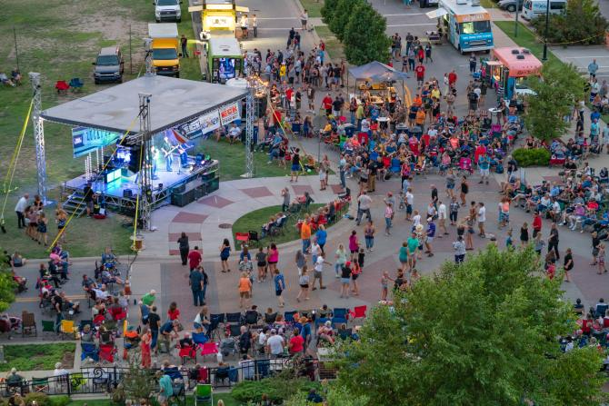 Aerial shot of people gathered around a stage at the WaterWalk fountains for the KEYN Summer Concert Series