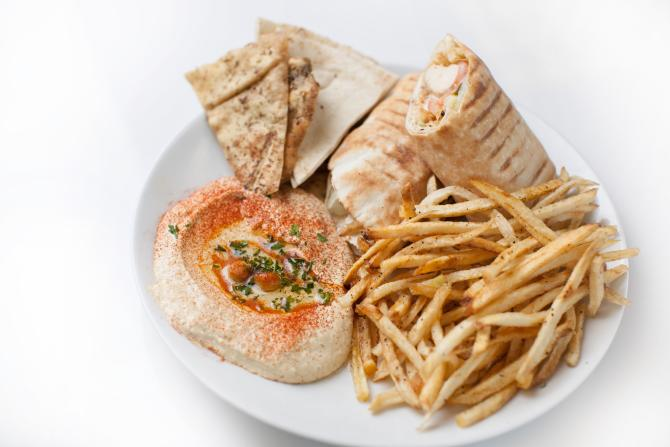 A plate full of chicken shawarma, hummus, flatbread, and fries from Meddys in Wichita