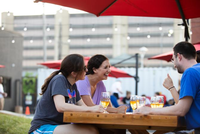 A group of friends share brews and laughs at a picnic table on Nortons Brewing Company's patio in Wichita