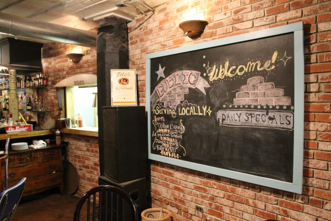 A chalkboard hangs on the brick wall at Public in Wichita